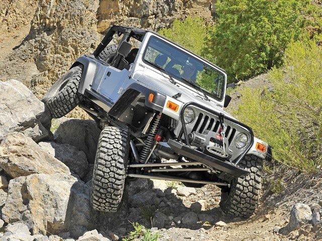 Jeep Wrangler crawling across large boulders