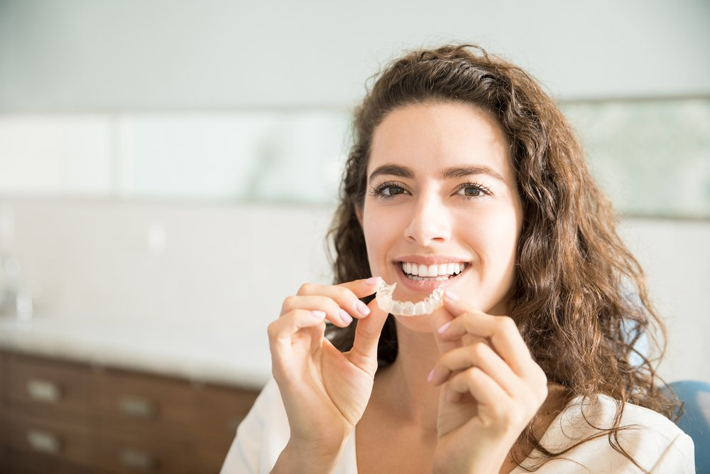 Portrait of beautiful patient holding orthodontic retainers in dental clinic - DIY Clear Aligners