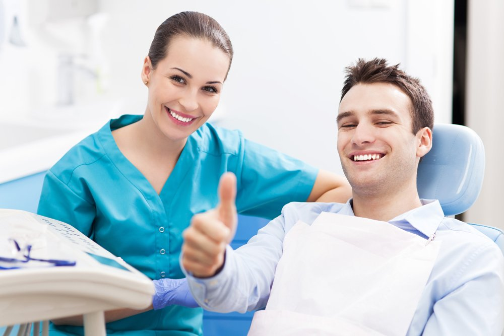 man giving a thumbs up at a dental office