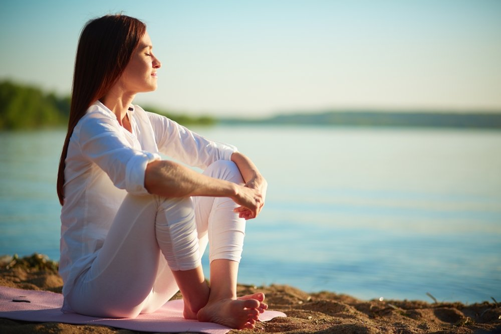 woman meditating on a beach - Idaho Falls TMJ treatment