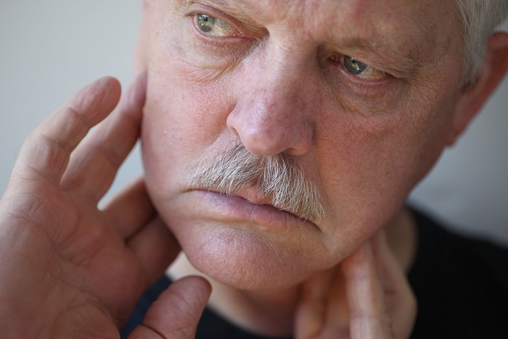 Older man massaging his jaw - Idaho Falls TMJ treatment