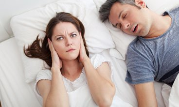 woman covering ears while man snores - non-surgical snoring solutions Idaho Falls