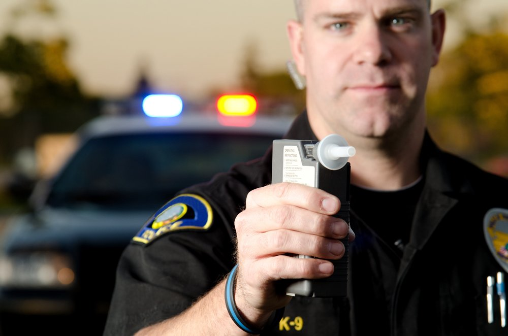 Police officer holding a breathalyzer