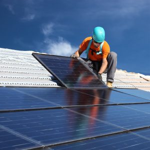 man installing solar panels on roof-min